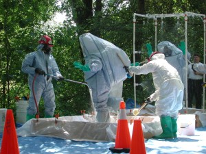 People in hazmat suits clean each other off