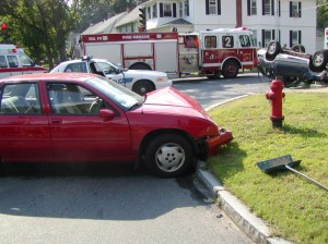 A fire truck and police car are on an accident scene where one car is upside down and the other has