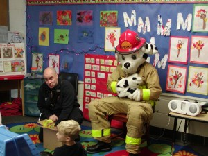 A person in a mascot uniform is dressed as a Dalmatian dressed as a firefighter while another man in