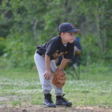 Little leaguer puts on big league face while waiting for the action on the game to pick up