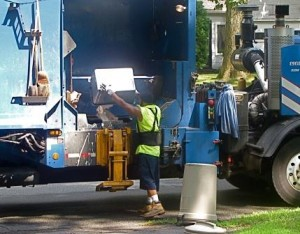 Sanitation Worker Putting Trash into Garbage Truck on Curbside